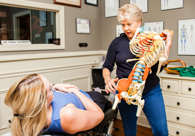 Chiropractor describes a procedure to a patient